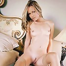Blonde model relaxes in her bedroom on the bed.